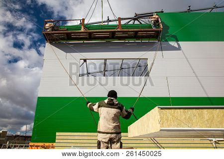 The builders are building a building of metal structures at a height in the construction cradle, in the foreground is a builder holding ropes against a blue sky. Violation of safety at a construction site poster