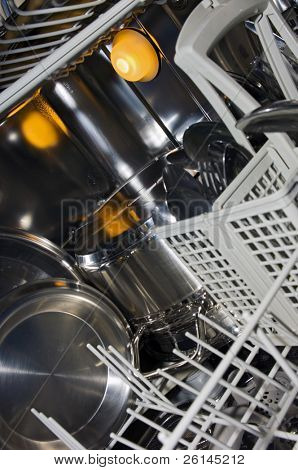 The interior of a dishwasher, with damp stainless steel, pots, pans and cutlery