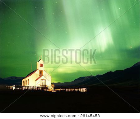 An illuminated church with the magnificent Aurora Borealis, or Northern Light lighting up the sky in Iceland