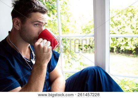 Handsome Doctor Or Male Nurse On Break Looking Out Of Window