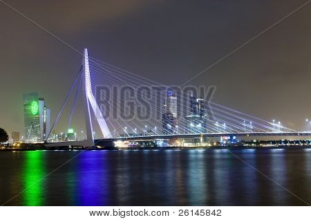 The famous Erasmus Suspension bridge with the Rotterdam skyline in the background at night, reflecting in the river Meuze