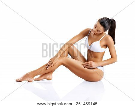 Young Girl With Perfect Body Touching Her Leg Sitting On White Background. Beauty & Skin Care Concep