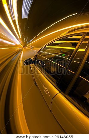 A car, seen from the outside, racing along a motorway at night