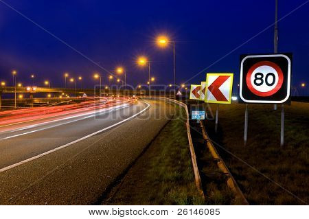 The warning signs on a motorway junction at night
