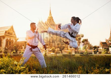 Female karate fighter trains kick in flight