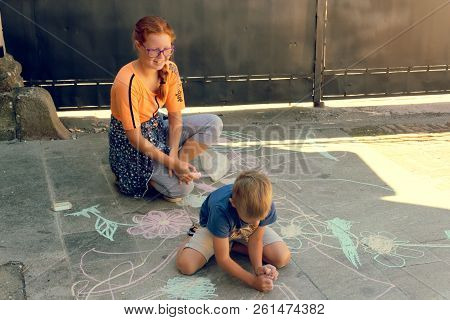 Montagnana, Italy August 27, 2018: Children Draw With Chalk On The Asphalt On A City Street.