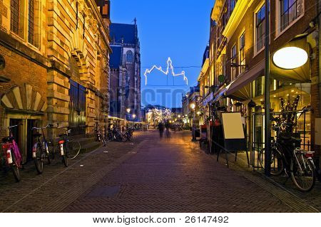 An alley with restaurants, displaying their specialties on a winter evening in Haarlem, the Netherlands