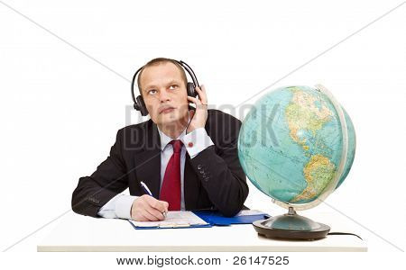 A businessman with a head set on listening attentively to a conversation in another language, represented by the globe on his desk