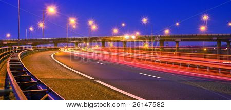 Cars breaking on an overpass of a motorway at night