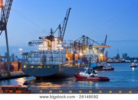 Diverse sleepboten en ondersteuning vaartuigen, helpen een grote container schip kunnen aanmeren af op de kade in de Rot