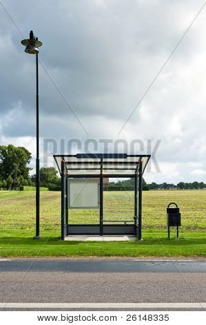 A bus stop is depicted standing in front of a field. Dark clouds indicate a storm is coming. There is no one viewable in the image. Vertically framed shot.