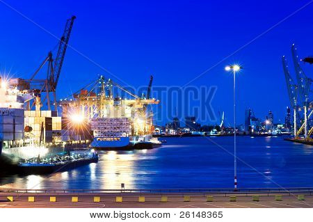 Image of a city port with intense blue saturated color. Boats are on the water, and the city of Rotterdam is viewable in the background. No people. Horizontally framed shot.