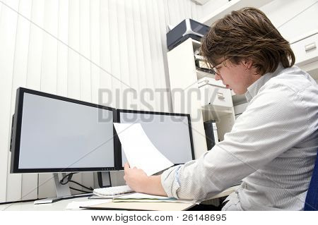 A designer, studying a ducument from the thick file in front of him behind his desk