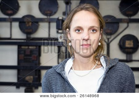 A portrait of a confident, slightly arrogant, looking woman, in front of an - out of focus - industrial grunge background