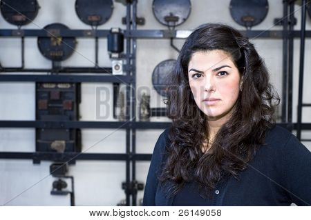 portrait of a young woman with long, dark brown hair against a grungy, industrial background, looking arrogant and full of self confidence