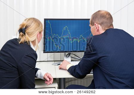 Two brokers analyzing (sales) trends, displayed on a flat screen monitor