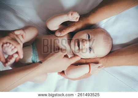 Massaging The Baby Very Gently. Newborn Baby Girl Or Boy. Newborn Care. Family Bonding With Infant B