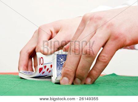 Dealer's hands shuffling cards during a poker game