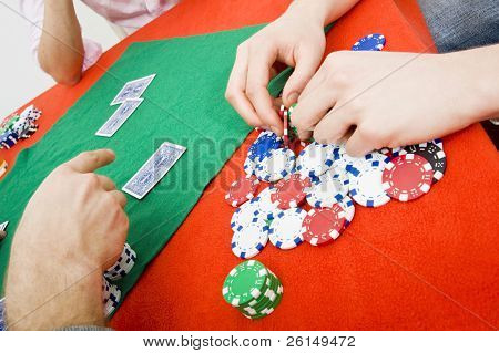 Details of a poker game with a player grabbing a handful of chips from his winnings