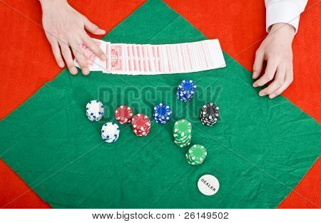 A dealer at a poker table preparing a new game