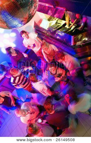 Busy dance floor in a nightclub near the DJ booth
