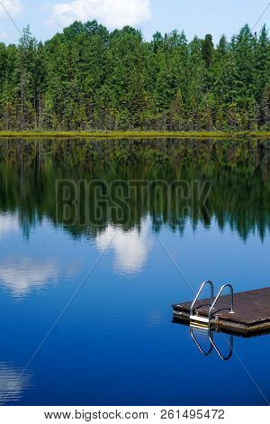 Beautiful Clear Blue Lake Water Reflecting Green Trees And Clouds With Wooden Dock And Ladder. Invit