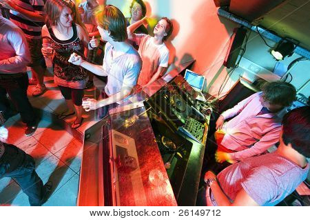 People dancing and flirting near the DJ booth at a nightclub