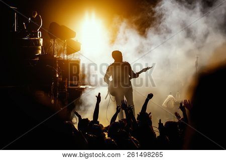Silhouette Of Guitar Player, Guitarist Perform On Concert Stage. Dark Background, Smoke, Concert Spo