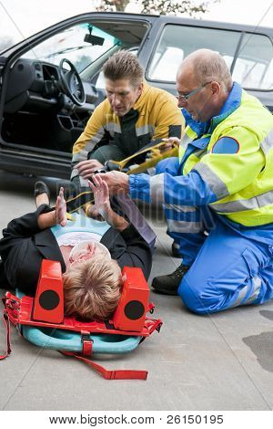 Multi-disciplinary medical team with a fireman and a paramedic, kneeling around a stretcher, and strapping an injured woman down