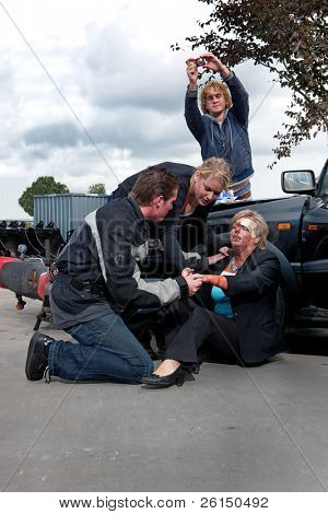 Bystanders checking up and providing first aid to an injured bleeding driver after a car crash. A man is taking pictures as amateur journalist for social media networks