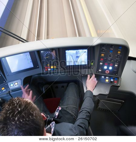 Train driver behind the dashboard controls of his carriage in the confined space of the cockpit poster