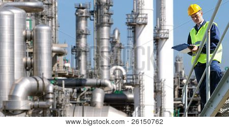 A petrochemical engineer, with a noteboard in his hand in front of a huge refinery