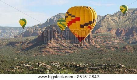 A Hot Air Balloon Foursome Soars Above The Red Rocks Of Sedona, Arizona, Usa