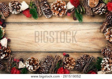 Winter background with rustic Christmas garland.Using pine cones,dried leaves and berries, twigs and other natural stuff to make Christmas decoration.