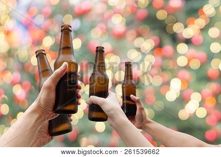 Hands Holding Beer Bottles And Happy Enjoying Harvest Time Together To Clinking Glasses At Outdoor P