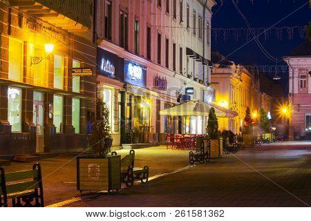 Uzhgorod, Ukraine - Oct 25, 2014: Korzo Street In Evening. Main Street Of The Old Town. Popular Tour