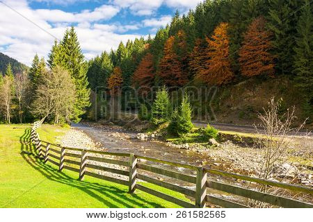 Camping Place Near The River. Wooden Fence On A Grassy Lawn Along The Shore. Road Under The Hill Wit