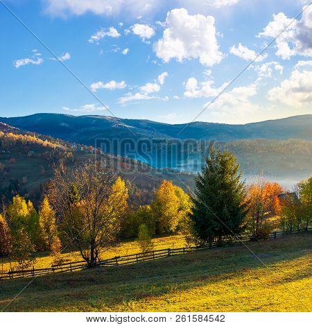 Beautiful Rural Area In Mountains. Gorgeous Autumn Sunrise With Beautiful Light, Fluffy Clouds On Th