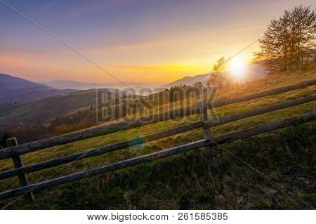 Beautiful Sunrise In Mountains. Countryside Scenery In Autumn. Fence Along The Rural Fields. Distant