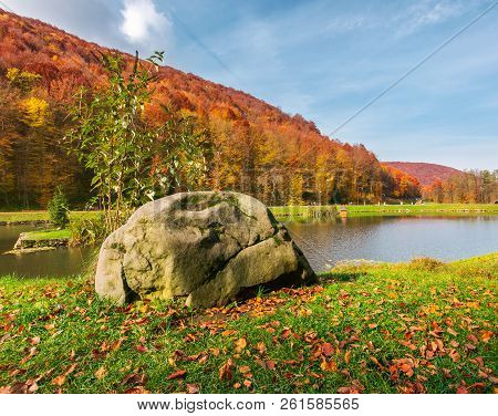 Boulder On The Shore Of A Lake. Lovely Autumn Scenery In Park. Forested Hills In Fall Colors