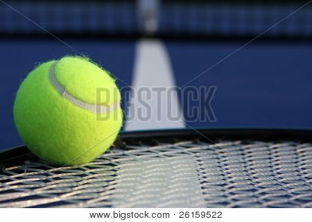 Tennis ball on racket strings