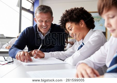 High School Tutor Giving Male Student Wearing Uniform One To One Tuition At Desk