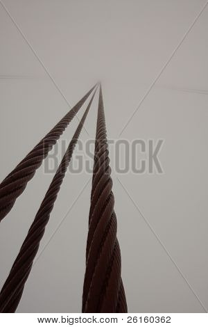 Cable of the Golden Gate Bridge leading off into the fog poster