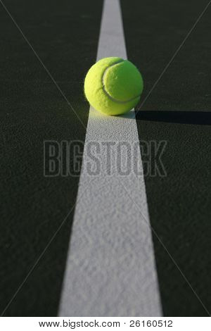 Tennis ball on the court line with copy space room in the foreground