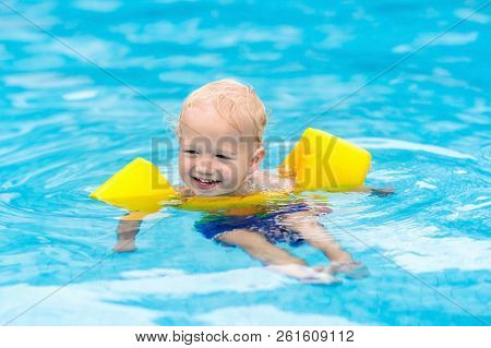 Baby In Swimming Pool. Kids Swim.