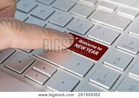 Close Up Of Finger On Keyboard Button With Welcome New Year Word. A Male Finger Presses A Color Butt