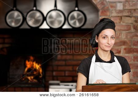Woman Chef Stand In The Kitchen Near Wood Oven