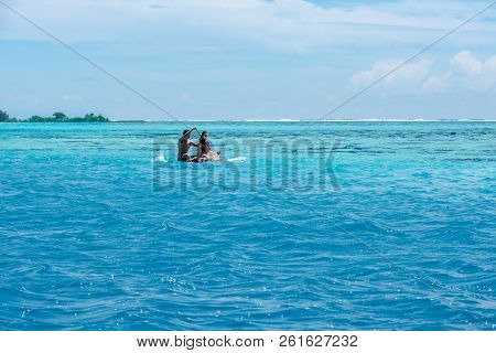 Moorea, French Polynesia--march 18, 2018. A Couple Navigates The Aqua Waters Of The Lagoon Around Mo