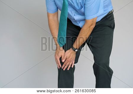 Pain In Knee. Close-up Businessman Leg With Painful Kneeson On Gray Background. Man Feeling Joint Pa