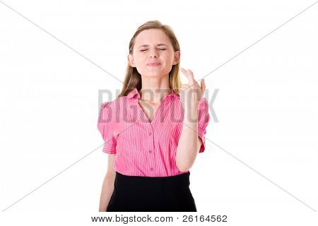 young attractive female holds her fingers crossed and eyes closed, wishful thinking, studio shoot isolated on white background